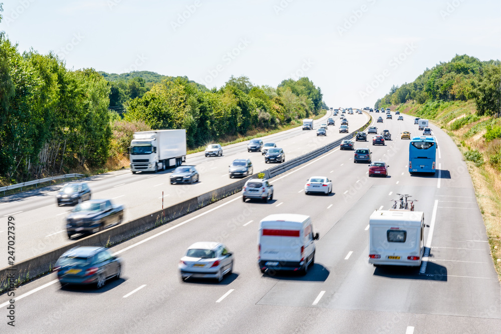 Fototapety, obrazy: Heavy but fluid traffic on the eight-lane A10 highway in France in the direction of Bordeaux by a hot summer day with cars, vans, trailers, buses and semitrailer truck driving.