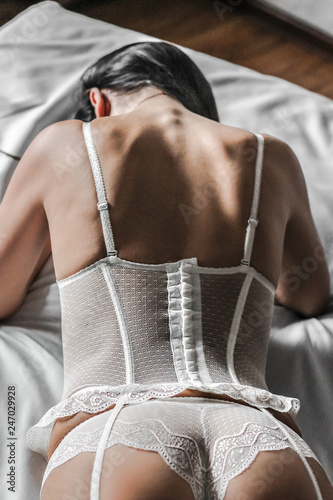 Fototapeta Sexy woman posing from behind in white lace lingerie. Boudoir. The fantasy image of sensual beauty returns to erotica. Beautiful buttocks and back. obraz