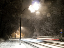 Car With Motion Blur Driving On A Snowy Street With Street Lights At Night