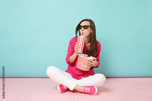 фотография Full length portrait fun woman in rose shirt, white pants sitting on floor watching movie film isolated on bright pink blue pastel wall background studio