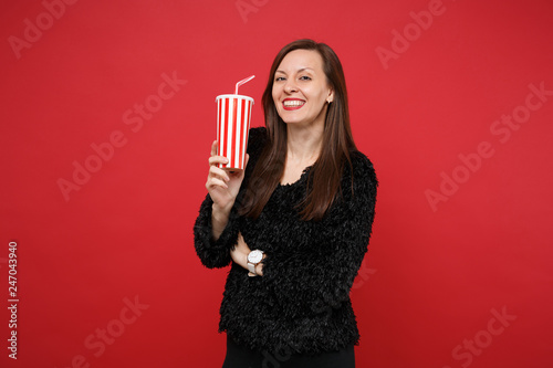 Fototapeta Portrait of smiling young girl in black fur sweater holding plastic cup of cola or soda isolated on bright red wall background in studio. People sincere emotions lifestyle concept. Mock up copy space. obraz na płótnie