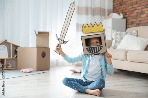 Cute little girl playing with cardboard armor in living room Wallpaper Mural