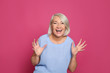 canvas print picture - Portrait of mature woman laughing on color background