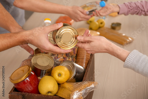 Volunteers taking food out of donation box on table, closeup