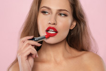 Young Woman Applying Red Lipstick On Color Background
