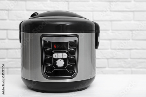 Modern electric multi cooker on table near brick wall