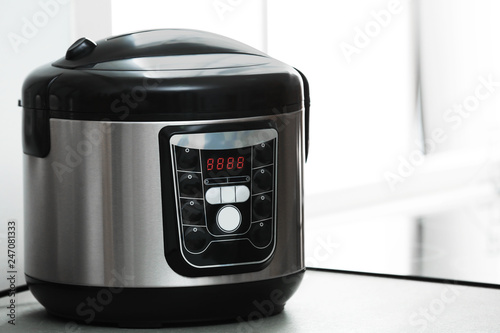 Modern electric multi cooker on table. Space for text