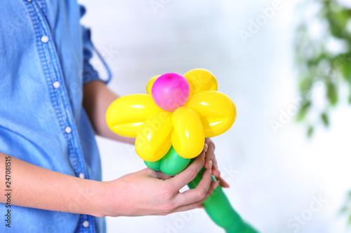 Woman making balloon figure on blurred background, closeup