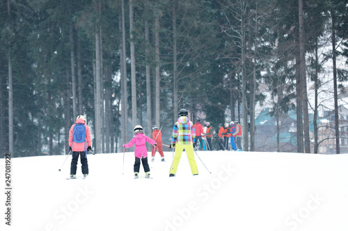 Skiers on slope at resort. Winter vacation