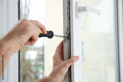 Fotografía  Construction worker adjusting installed window with screwdriver indoors, closeup