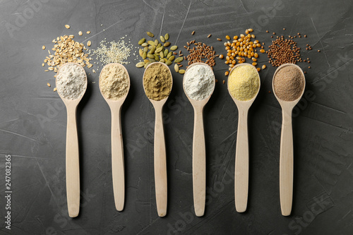 Spoons with different types of flour and ingredients on grey background, top view
