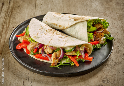 Fototapeta Tortilla wraps with fried chicken meat and vegetables obraz