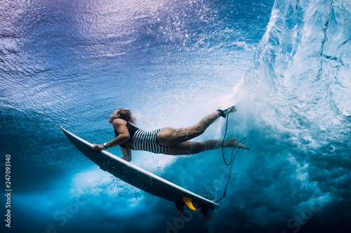 Foto  Surfer woman with surfboard dive under wave