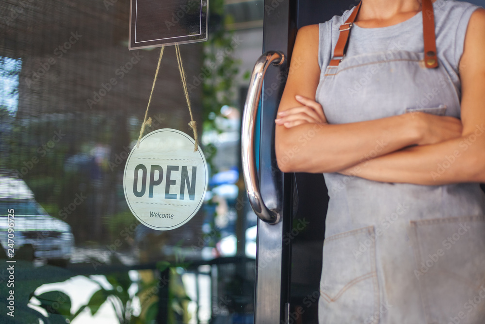 Fototapety, obrazy: The woman is a waitress in an apron, the owner of the cafe stands at the door with a sign Open waiting for customers. Small business concept, cafes and restaurants