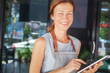 The woman is a waitress in an apron, the cafe owner is holding a tablet with a menu. Small business concept, cafes and restaurants