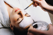 Lovely Woman With Closed Eyes Lying On Spa Bed While On Face Is Applying White Mask With A Brush In A Spa Salon.