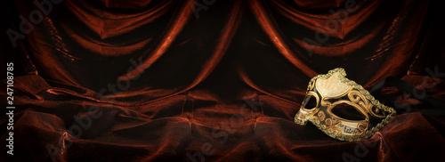 Photo of elegant and delicate gold venetian mask over dark velvet and silk background.