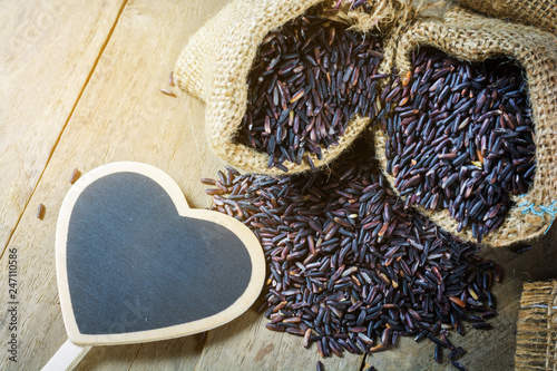Brown rice, riceberry organic food in hemp sack with heart shape blackboard empty for text on wooden background, healthy food and diet concept.