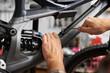 Cropped shot of repairman working in bicycle repair shop, repairing mountain bike using special equipment