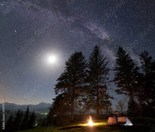 Fototapeta Night camping in mountains. Tourist tent by burning campfire under amazing beautiful dark blue starry sky, full moon and Milky way. High pine trees on background. Outdoor activity, tourism concept obraz na płótnie