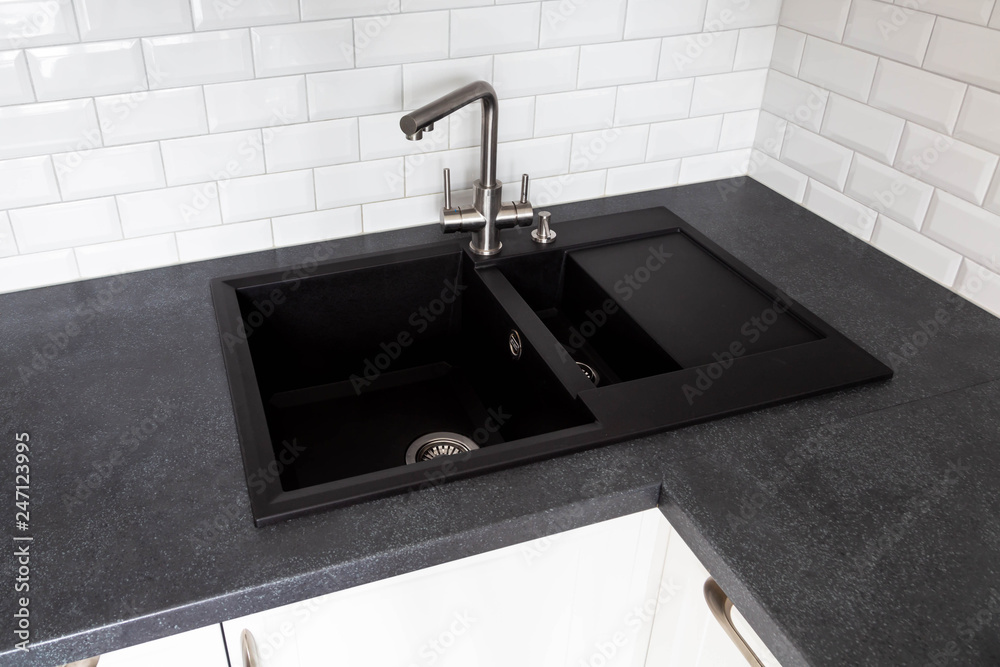 Fototapeta Black granite sink and a mixer mounted on a black countertop