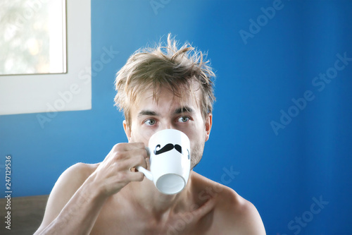 Fotografie, Obraz  just woke up and disheveled man drinking fresh coffee or tea from mug with paint