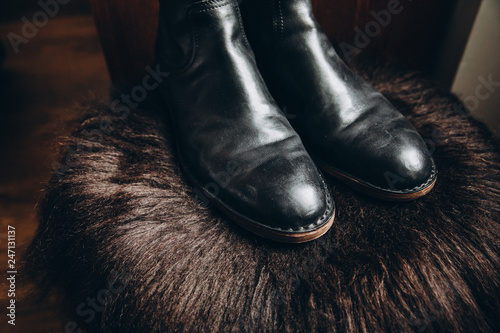 Photo men's black leather shoes stand on the bearskin