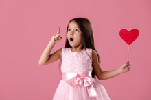 Portrait Of Cute Little Girl In Pink Dress Holding Paper Heart, Pointing Up And Having Idea On Pink Background. St. Valentine's Day
