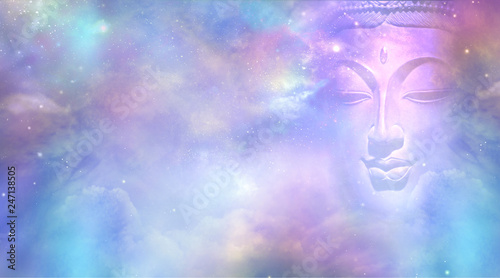 Cosmic Buddha Vision Cloud scape - Semi transparent Buddha face with closed eyes amongst the celestial heavens providing a beautiful  pink and blue sky background   - 247138505