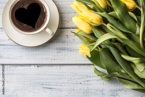 Top of view cup form coffee with heart and spring tulips on wooden table