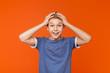 Leinwandbild Motiv Surprised excited little boy holding hands on head