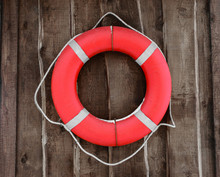 Red And Round Lifebuoy Hanging On Brown Wooden Wall