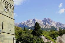 Ancient Castle On The Background Of Mountains And Blooming Garden