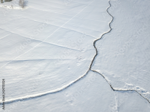 Aluminium Prints Forest river Aerial view of snow covered plain with brook flowing in straight line through landscape.
