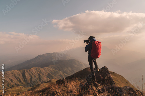 Foto auf AluDibond Lachs Young man traveler with backpack taking a photo on mountain, Adventure travel lifestyle concept