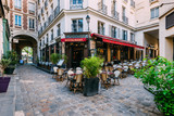 Fototapeta Uliczki - Cozy street near Boulevard San-German with tables of cafe  in Paris, France. Architecture and landmark of Paris. Paris cityscape