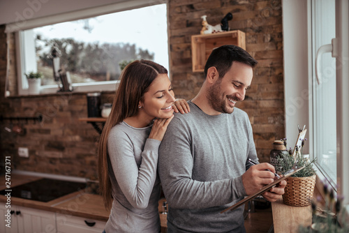 Portrait of a cute millennial spouses writing a list at modern cozy apartment Tableau sur Toile