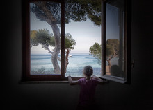 Little Girl Looks At The Sea Through The Glass Of The Window