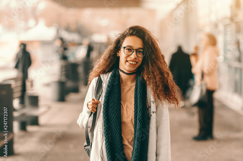 Foto  Smiling beautiful mixed race hipster girl with long curly hair stranding at the bus station in spring