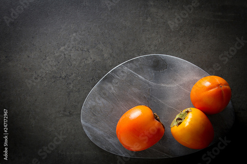 fresh persimmon on a gray stone background