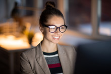 Cheerful Office Manager With Toothy Smile Looking At Computer Screen While Sitting In Darkness And Working Overtime
