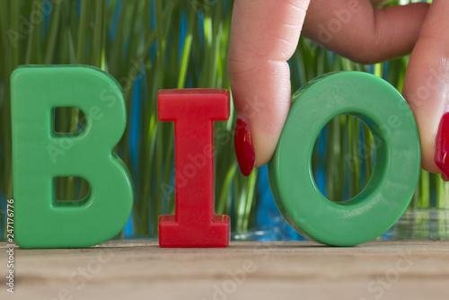 Bio word from plastic letters in front of green natural background