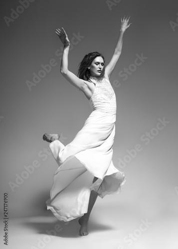 Valokuvatapetti woman dancing classic dance in white dress on gray background