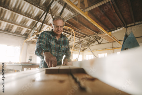 Senior male carpenter working in carpentry workshop