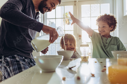 Smiling father pouring milk in to bowls for breakfast Fototapet