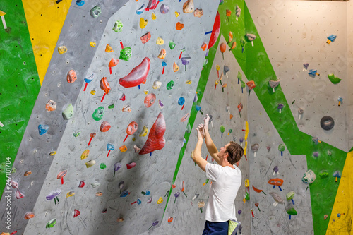 Fotografiet  climber explores and develops a route on a climbing wall in the boulder hall
