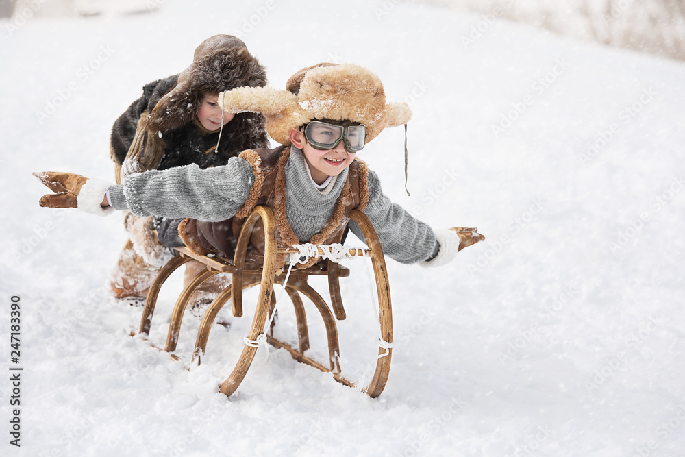 Fototapeta Children slide down hills on sleds
