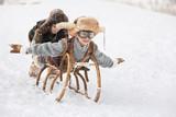 Children slide down hills on sleds