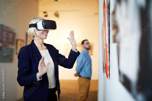Photo Waist up portrait of contemporary smiling woman wearing VR headset in art galler
