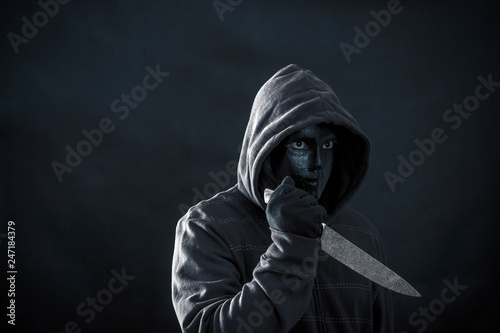 Fotomural  Hooded man with black mask holding knife in the dark